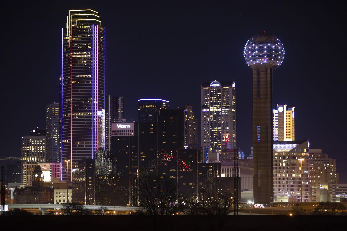 """The Bank of America building in downtown Dallas is seen lit in Southwest Airlines colors in memory of Herb Kelleher as Reunion Tower shows his name """"Herb"""" on Friday, Jan. 4, 2019."""