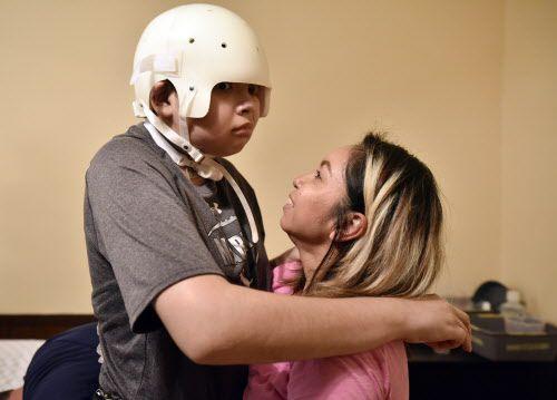 Esteban Monreal, 16, se para con la ayuda de su madre Tomasita Gómez mientras su padre le prepara un arnés para que pueda caminar. Ben Torres/ Especial para Al Día