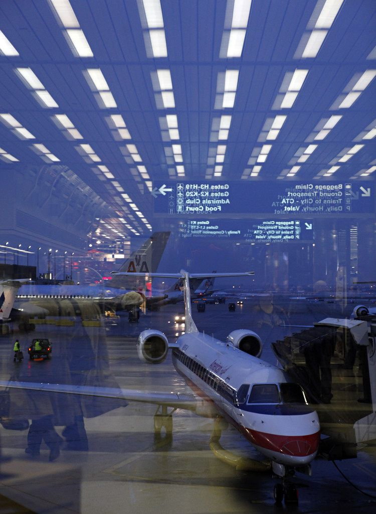 An American Eagle regional jet in front of larger American Airlines planes while the concourse is reflected in the window of Terminal 3 at O'Hare International Airport.