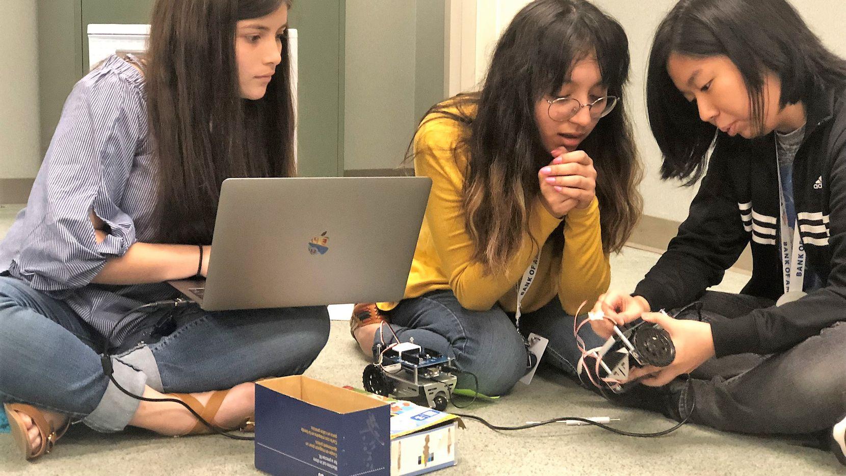 Joselin Barbosa (centro) con sus compañeras Jesel Reyes (izq.) y Youngone Lee (der.) aprenden cómo programar un robot en Addison.