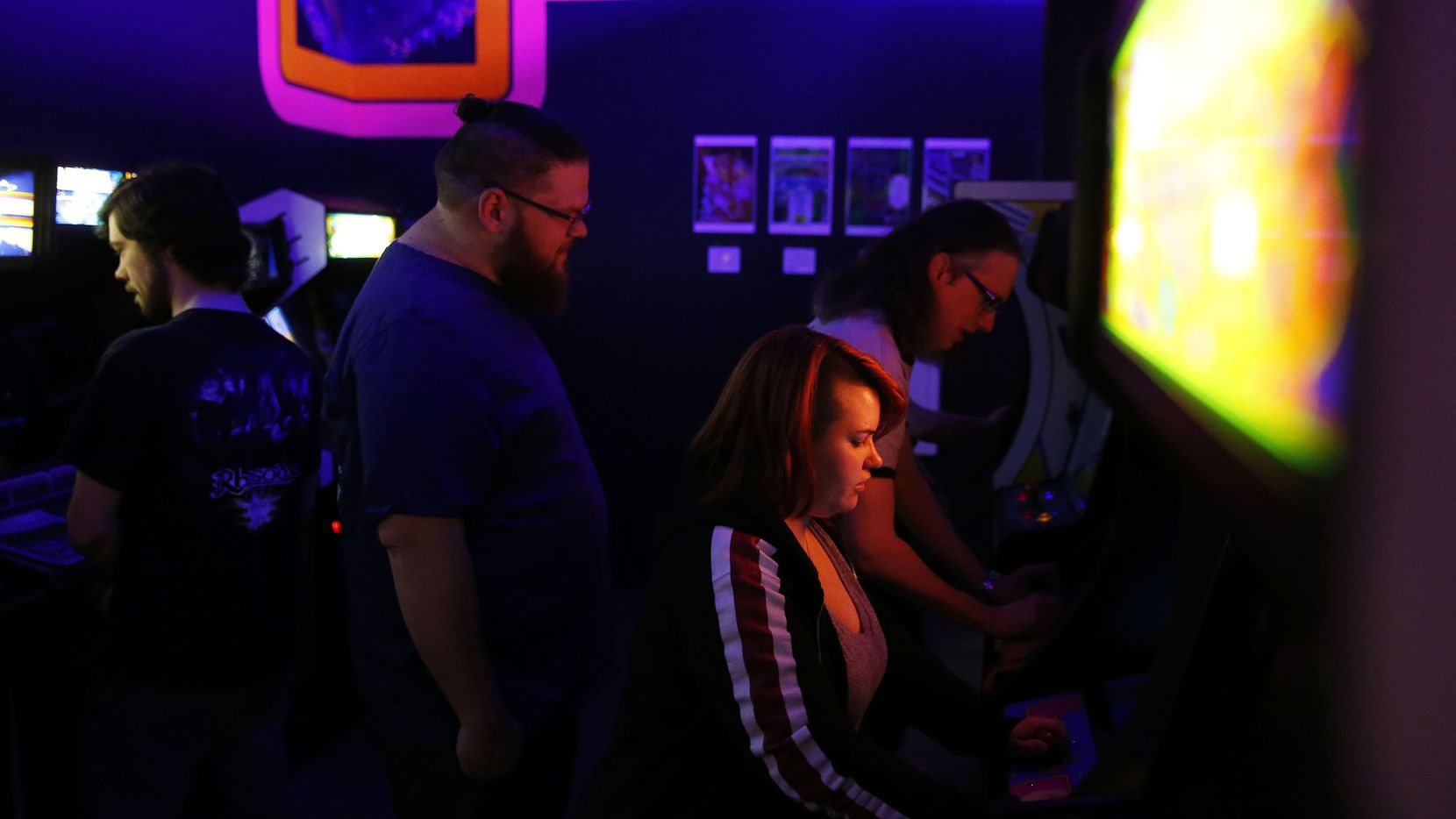 Jess Alvarez (center), of Irving, Texas, plays Ms. Pac-Mac during the soft opening of the National Videogame Museum. (Andy Jacobsohn/Staff Photographer)