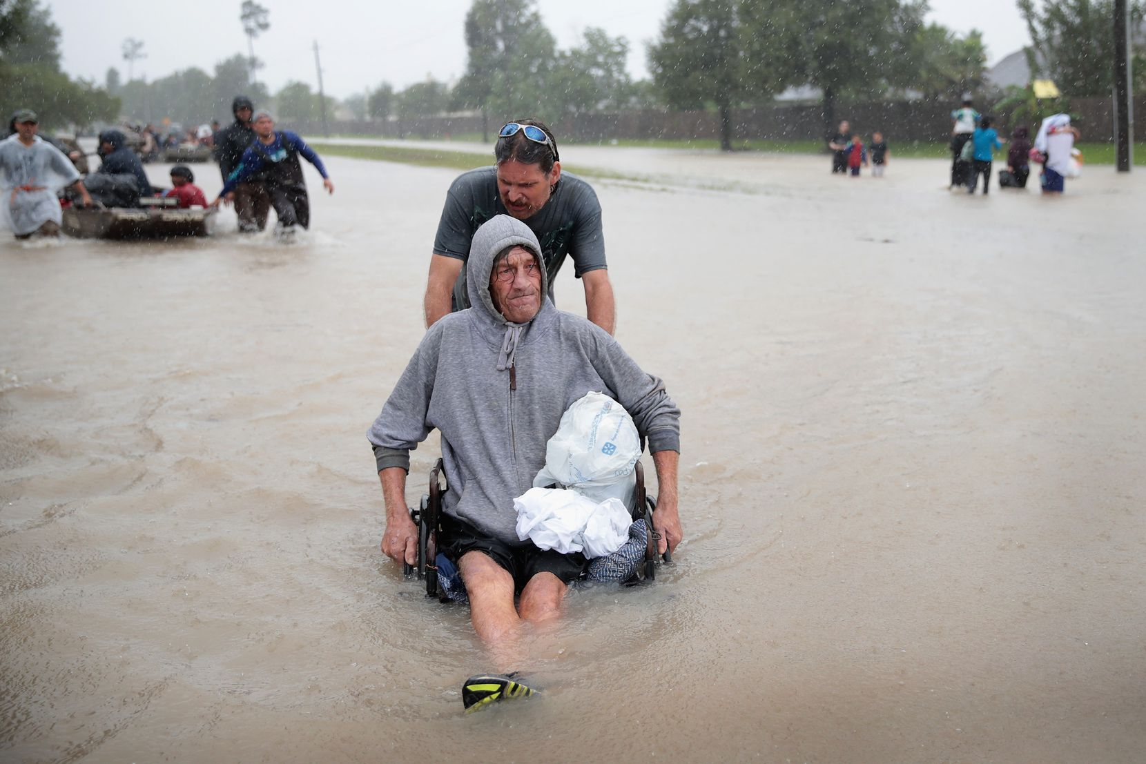 People make their way out of a flooded neighborhood after it was inundated with rain water, remnants of Hurricane Harvey, on August 28, 2017 in Houston, Texas.