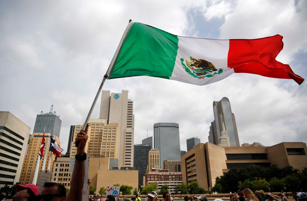 A protester waves the Mexican flag during Saturday's rally in Dallas.