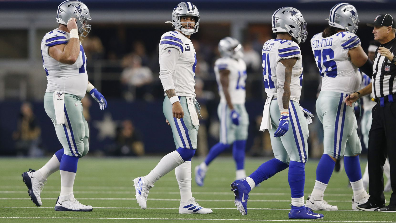 Dallas Cowboys quarterback Dak Prescott (4) looks back as he walks to the bench after Buffalo Bills defensive tackle Ed Oliver (91) stripped the ball from him forcing a turnover during the first half of play at AT&T Stadium in Arlington, Texas on Thursday, November 28, 2019. Dallas Cowboys center Travis Frederick (72), Dallas Cowboys running back Ezekiel Elliott (21) and Dallas Cowboys offensive guard Xavier Su'a-Filo (76) make their way to the bench as well. (Vernon Bryant/The Dallas Morning News)