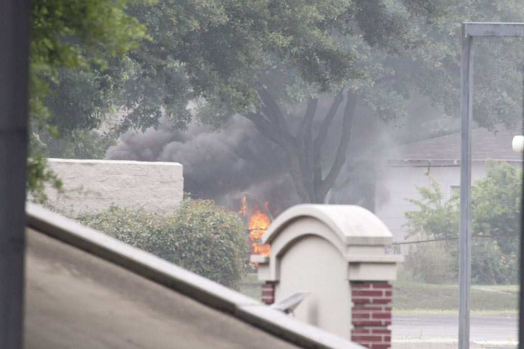 The van used by the suspect in the Dallas Police Department shooting goes up in flames after a bomb squad worked the scene at E. Palestine Street and Interstate 45 in Hutchins on Saturday.