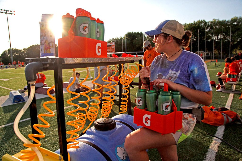 Student athletic trainer Jamie Owen, 16, readies a water station before practiceduring the first week of football practice for Celina High School at Bobcat Stadium on Wednesday morning, August 8, 2018. (Stewart F. House/Special Contributor)