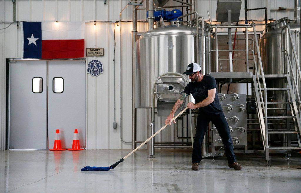 Nate Seale, head brewer mops the floor of the brewhouse at Family Business Beer Company in Dripping Springs, Texas on Saturday, February 24, 2018. (Vernon Bryant/The Dallas Morning News)