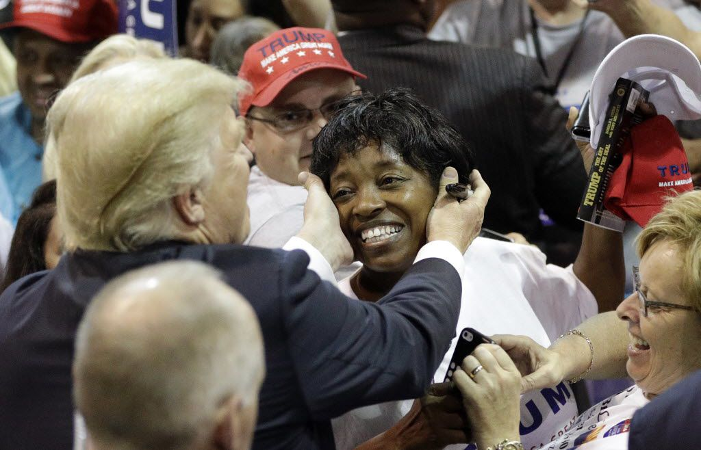 Republican presidential candidate Donald Trump reaches out to hug a supporter after a rally on June 17, 2016, in The Woodlands, Texas.