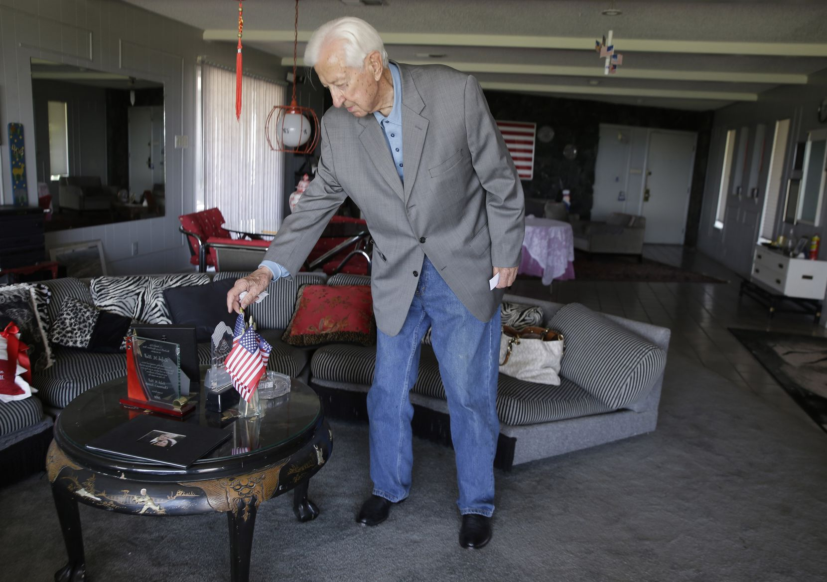 Rep. Ralph Hall adjusted miniature American flags on a coffee table at his home in Rockwall in May, 2014.
