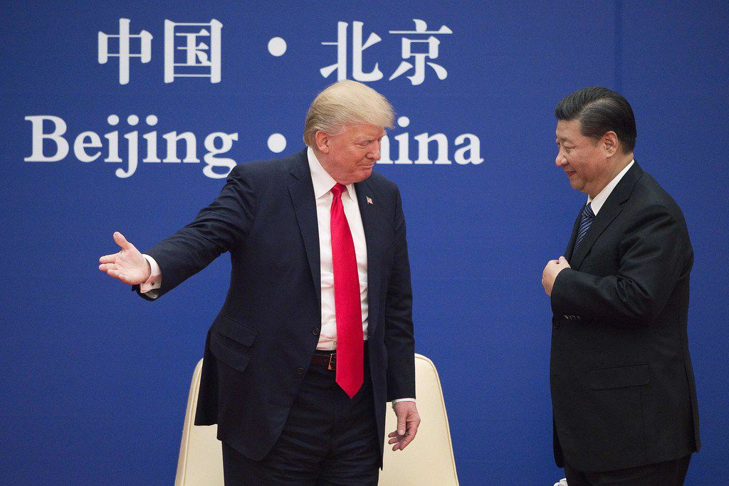 """(FILES) In this file photo taken on November 8, 2017 US President Donald Trump (L) gestures next to China's President Xi Jinping during a business leaders event at the Great Hall of the People in Beijing. - US President Donald Trump said June 18, 2019 he had a positive phone conversation with his Chinese counterpart Xi Jinping and that they will hold an """"extended meeting"""" next week at the G-20 summit."""
