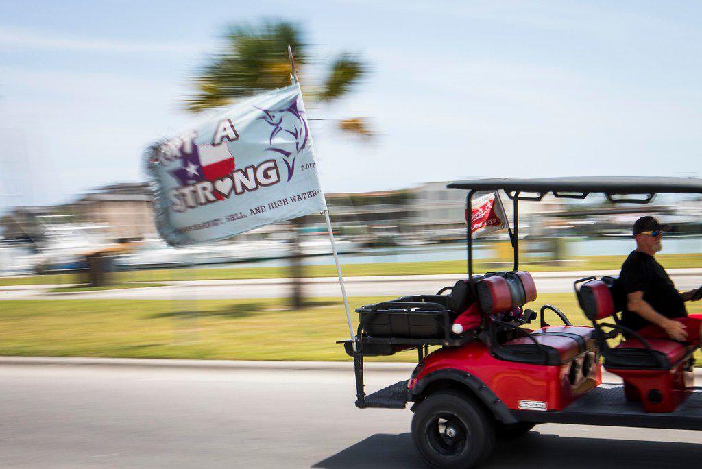 "A ""Port A Strong"" flag flies behind a golf cart rolling through Roberts Beach Park in Port Aransas on the Texas Gulf Coast."