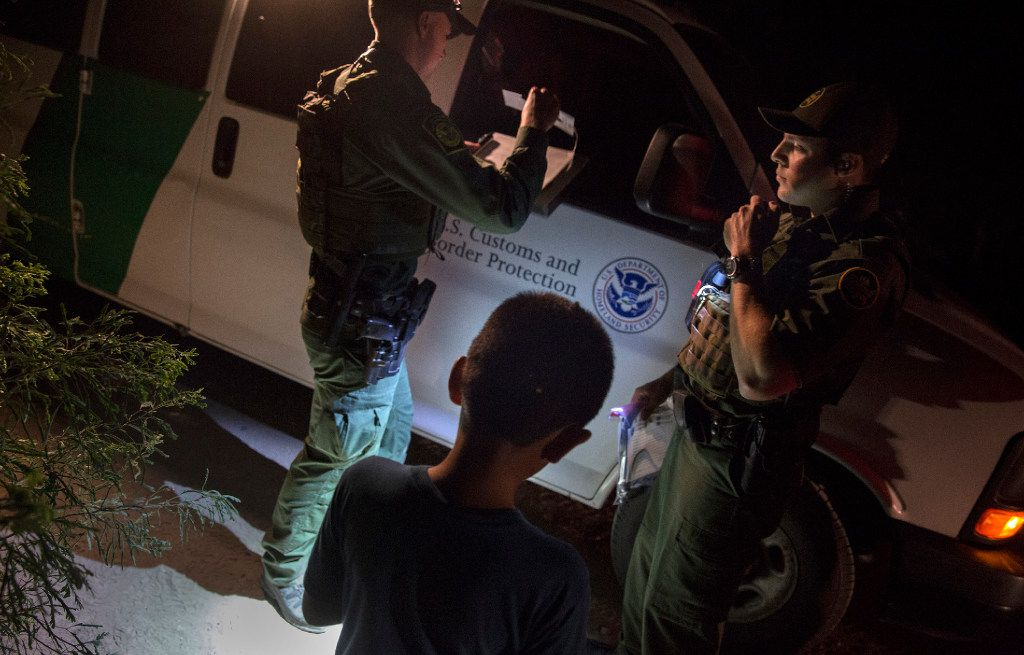 Border Patrol agents Edgar Cano (right) and Richard Schweitzer processed unaccompanied minor Darwin, 11, for transportation after the boy illegally crossed the Rio Grande on a raft in Hidalgo, Texas, on March 24, 2017.