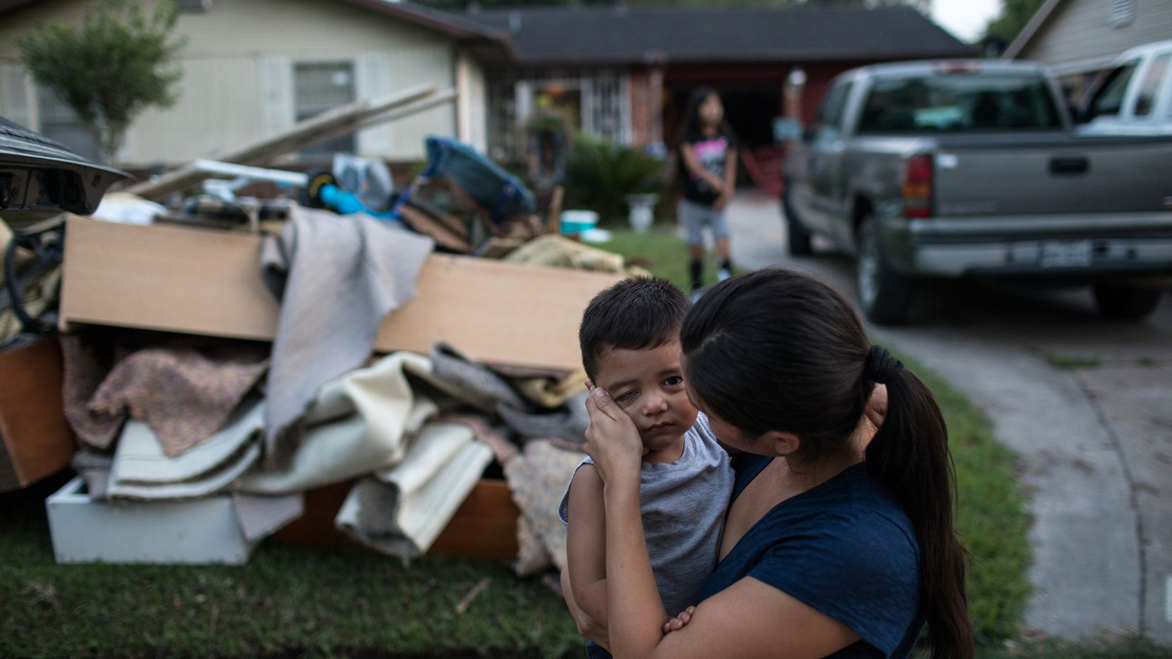 Sabrina Rodriguez wiped away a tear as she comforted her son, Eder Cantero, 2, outside their flood-damaged home near Halls Bayou in Houston on Saturday. (Tamir Kalifa/The New York Times)