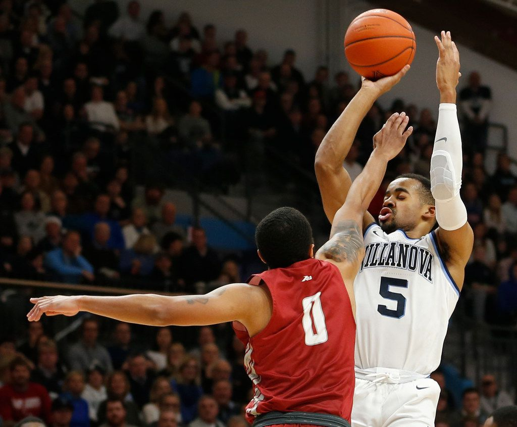 Villanova guard Phil Booth (5) is fouled by Saint Joseph's guard Lamarr Kimble (0) during the second half of an NCAA college basketball game, Saturday, Dec. 8, 2018, in Villanova, Pa. Villanova won 70-58. (AP Photo/Laurence Kesterson)