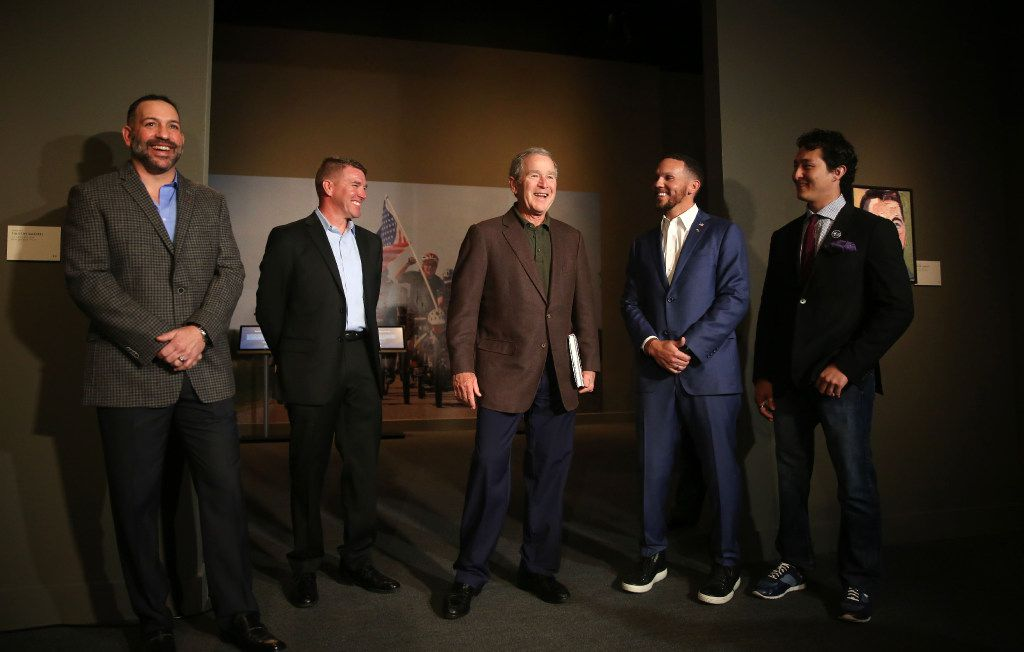President George W. Bush (center) stands next to veterans  he has painted (from left) 1st Sgt. Robert Ferrara, Chief Warrant Officer James Williamson, Staff Sgt. Johnnie Yellock and Sgt. Jay Fain during a media preview of the Portraits of Courage exhibit at the George W. Bush Presidential Center in Dallas (Rose Baca/The Dallas Morning News)