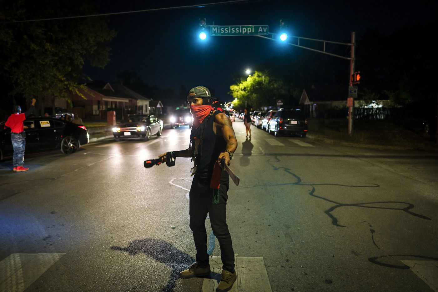 A masked man man carrying a machete directs traffic in 1200 block of East Allen Avenue during a community vigil for Atatiana Jefferson on Sunday, Oct. 13, 2019, in Fort Worth.