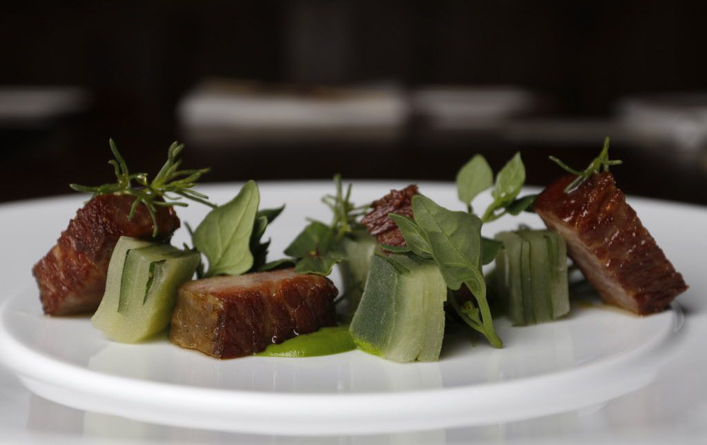 Gyutoro, a 72-hour short rib set on spinach puree, is garnished with slabs of green apple sliced finely like the pages of a book; inserted between some of the pages are pieces of Thai basil.