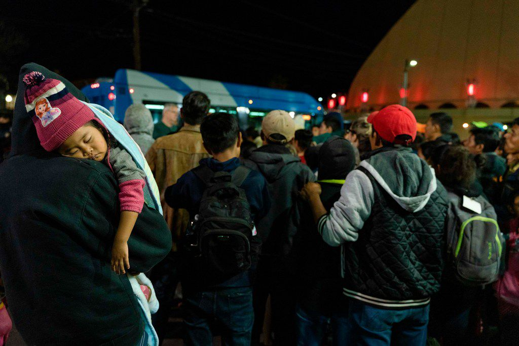 Asylum seekers stand at a bus stop after they were dropped off by Immigration and Customs Enforcement at the Greyhound station in downtown El Paso late on Sunday. The group of around 200, mostly made up of Central Americans, were left without money, food and means of communication. Volunteers from Annunciation House and other local churches came to aid and find a place to house them for the night.