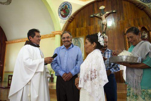 Francisca Santiago (der.) y su esposo Pablo Ibarra (centro) sonríen mientras intercambian los votos matrimoniales frente al sacerdote Domingo García Martínez en la iglesia de Santa Ana.
