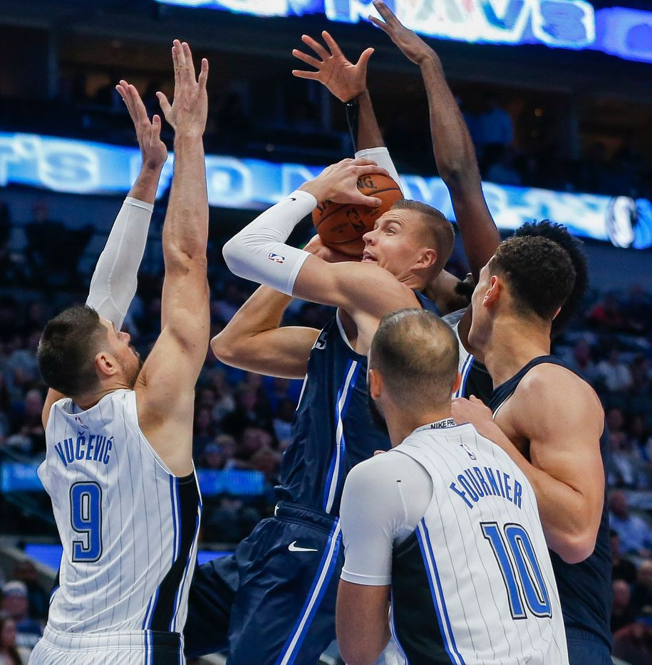 Dallas Mavericks forward Kristaps Porzingis (6) attempts to get a shot past Orlando Magic center Nikola Vucevic (9) and guard Evan Fournier (10) during the first quarter of a game against the Orlando Magic on Wednesday, Nov. 6, 2019 at American Airlines Center in Dallas.