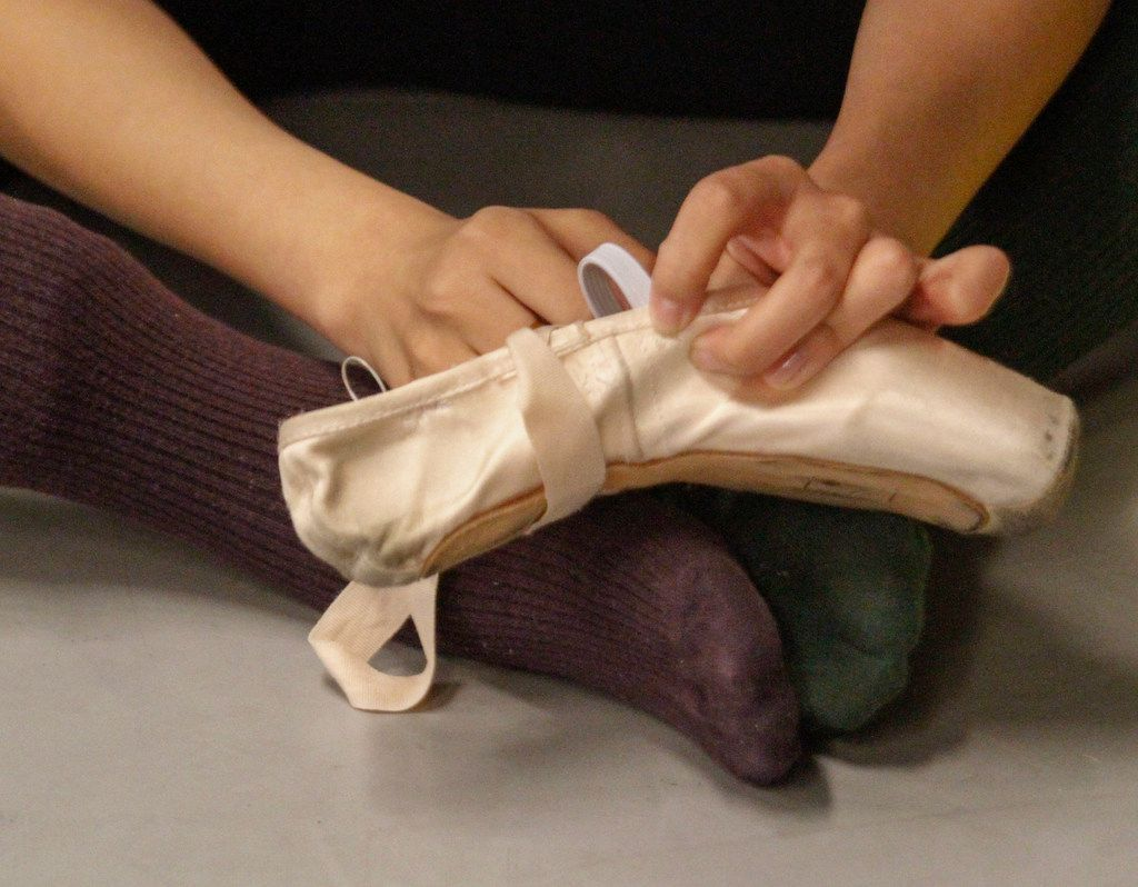 Wang Yuanyuan, artistic director of Beijing Dance Theater, repairs a pointe shoe being used in her new piece Facing the Ocean. The lighthearted duet was one of two new works by Wang that premiered at the TITAS Command Performance.