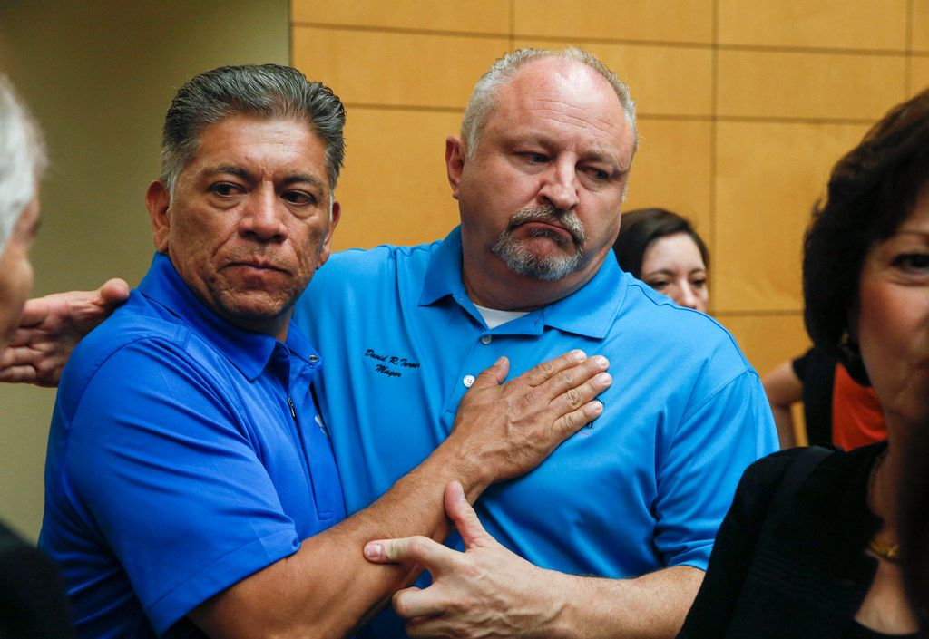 Midland, Texas Mayor Jerry Morales, left, embraces Odessa, Texas Mayor David Turner following a press conference at the University of Texas Permian Basin on Sunday, Sept. 1, 2019 in Odessa, Texas. At least seven people died after more than 20 people were shot Saturday when a gunman hijacked a postal truck and began shooting randomly in the Odessa area of West Texas, authorities say. (Ryan Michalesko/The Dallas Morning News)
