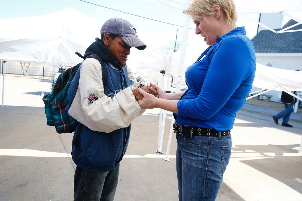 Sarah Slack (right) prayed with Arhonda Cokefield after the service at the SoupMobile Church for the homeless in Dallas on Feb. 4, 2018.