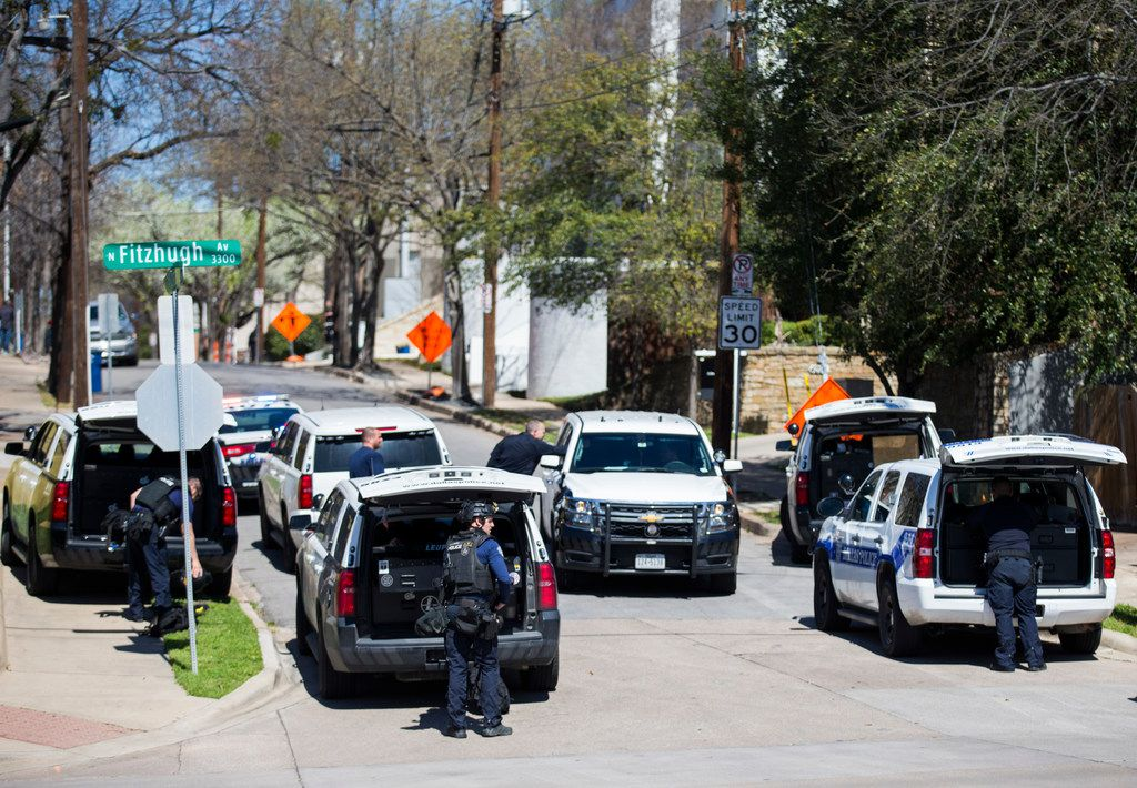 SWAT officers return to their vehicles after an incident near the corner of Fitzhugh and Buena Vista on Thursday in Dallas.