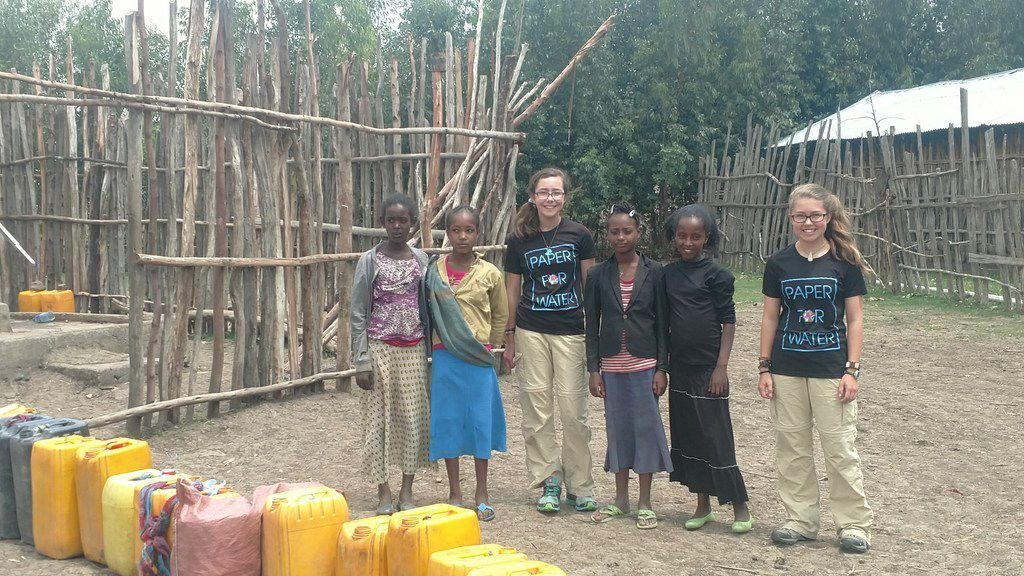 Katherine Adams, center, with her sister, Isabelle, meet with village girls in Ethiopia, where Paper for Water funded a well. Photo taken on May 24, 2017, while the Adams family was touring the world.