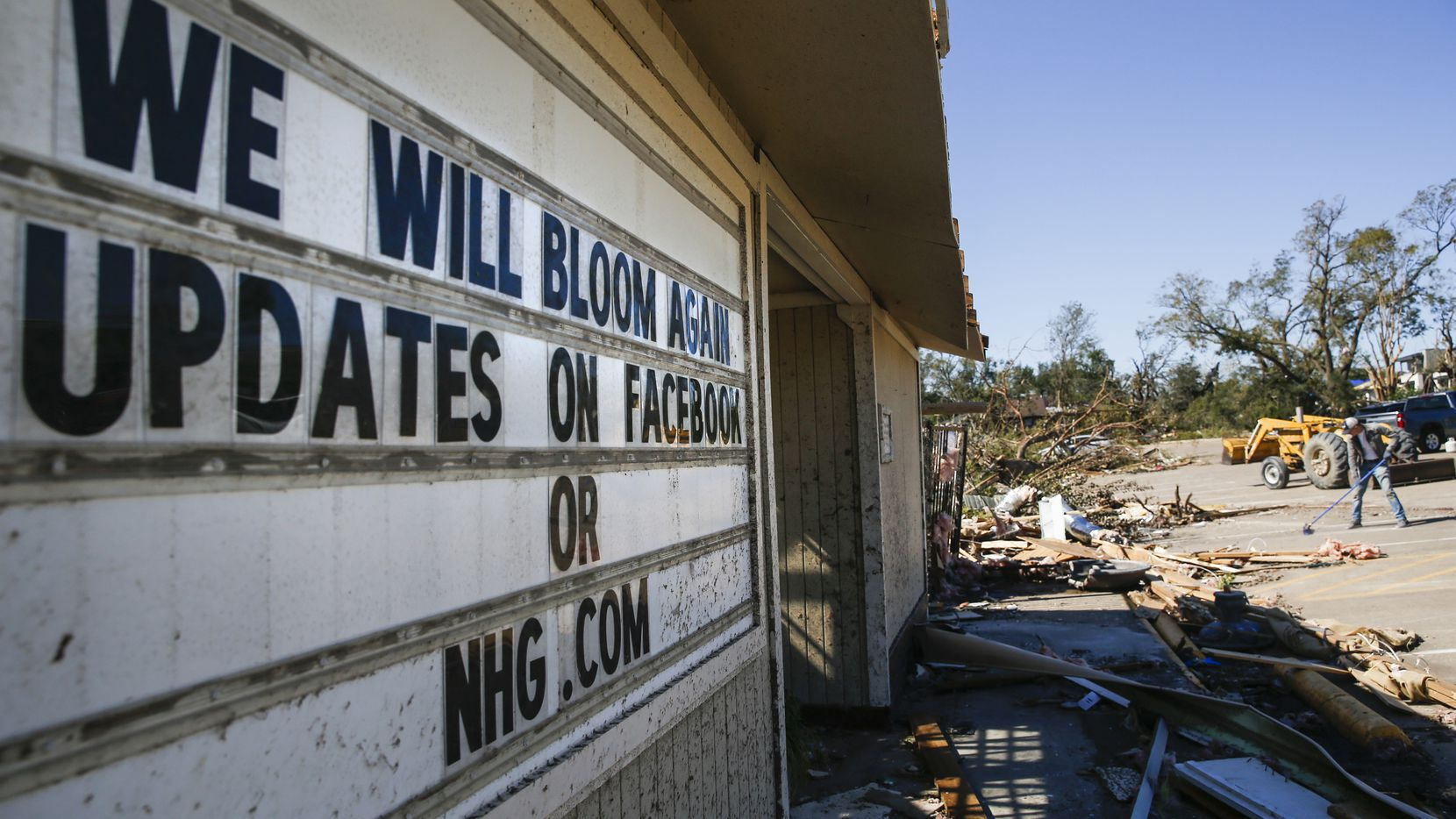 """A sign at North Haven Gardens reads """"We will bloom again"""" as workers continue to clear debris along North Haven Road in Dallas on Tuesday."""