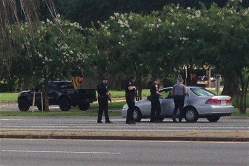 Las autoridades hablan con un conductor cerca de la zona donde varios agentes fueron heridos a menos de 1,600 metros de la sede policial en Baton Rouge, Louisiana, domingo 17 de julio de 2016. (AP Foto/Mike Kunzelman)