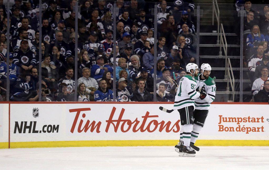 Dallas Stars' Tyler Seguin (91) and Jamie Benn (14) celebrate after Seguin scored against the Winnipeg Jets during the second period of an NHL hockey game Monday, March 25, 2019, in Winnipeg, Manitoba. (Trevor Hagan/The Canadian Press via AP)