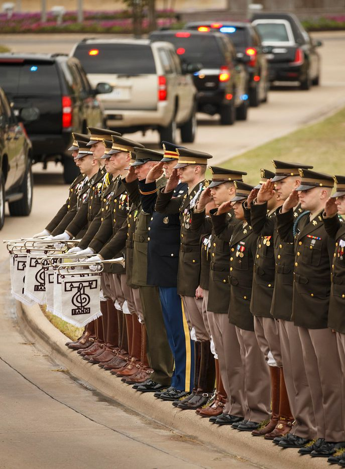 Members of the Texas A&M Corps of Cadets salute the motorade following the hearse carrying former first lady Barbara Bush as it nears her husband's presidential library at the university on Saturday, April 21, 2018, in College Station, Texas. After an invitation-only funeral in Houston, Bush, who died on Tuesday, was buried at a gated plot near the library. 700 members of the Corps of Cadets lined the Barbara Bush Drive leading up to the library.