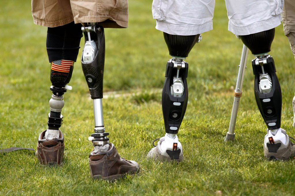 The prosthetic legs of Dana Bowman, U.S. Army retired Sgt. First Class and CEO of the HALO for Freedom Warrior Foundation (left), are seen alongside a fellow injured soldier (not named) after a skydive jump over Texas Motor Speedway on March 1, 2013.