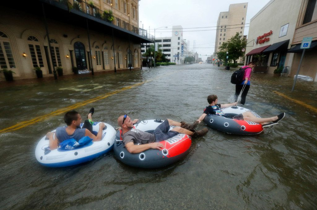 John Hall (left), Shayne Hoffstettler (middle) and Grant Boswell get pulled through the flooded and historic Strand District of Galveston, Texas after punishing overnight rains from Tropical Storm Harvey inundated the island, Tuesday, August 29, 2017. (Tom Fox/The Dallas Morning News)