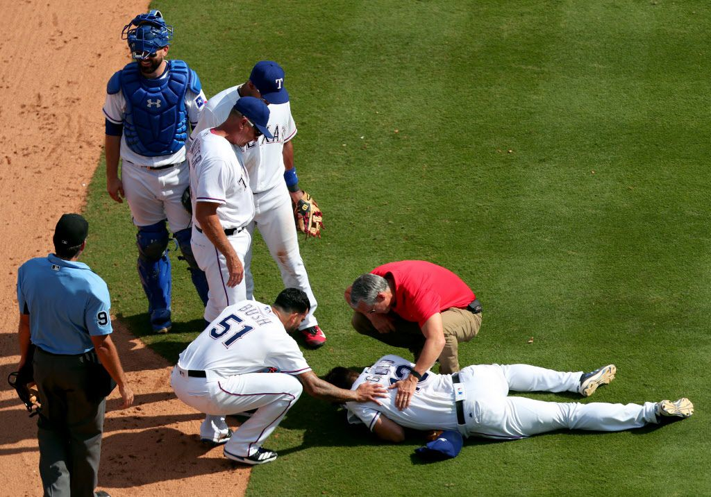 ARLINGTON, TX - AUGUST 20:  Joey Gallo #13 of the Texas Rangers lays on the field after colliding with Matt Bush #51 of the Texas Rangers while fielding the ball against the Chicago White Sox in the top of the eighth inning at Globe Life Park in Arlington on August 20, 2017 in Arlington, Texas.  (Photo by Tom Pennington/Getty Images)