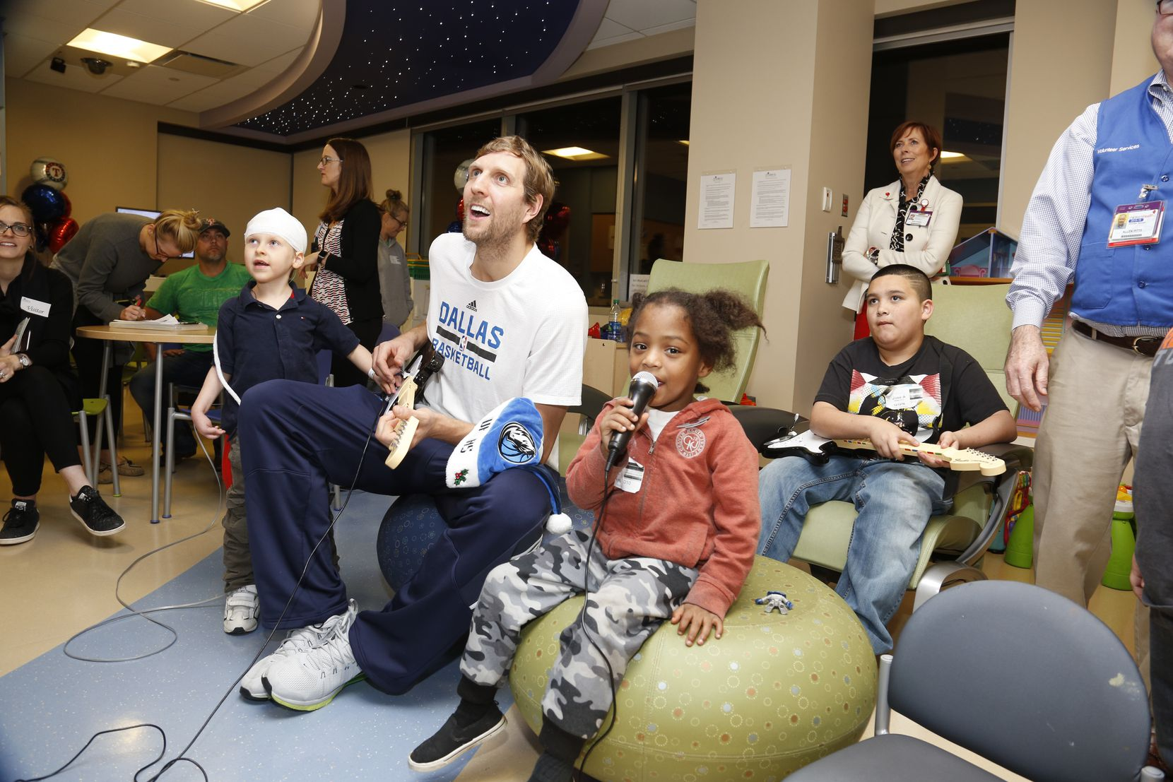 Dirk Nowitzki plays Guitar Hero with patients at Children's Medical Center on a recent visit.