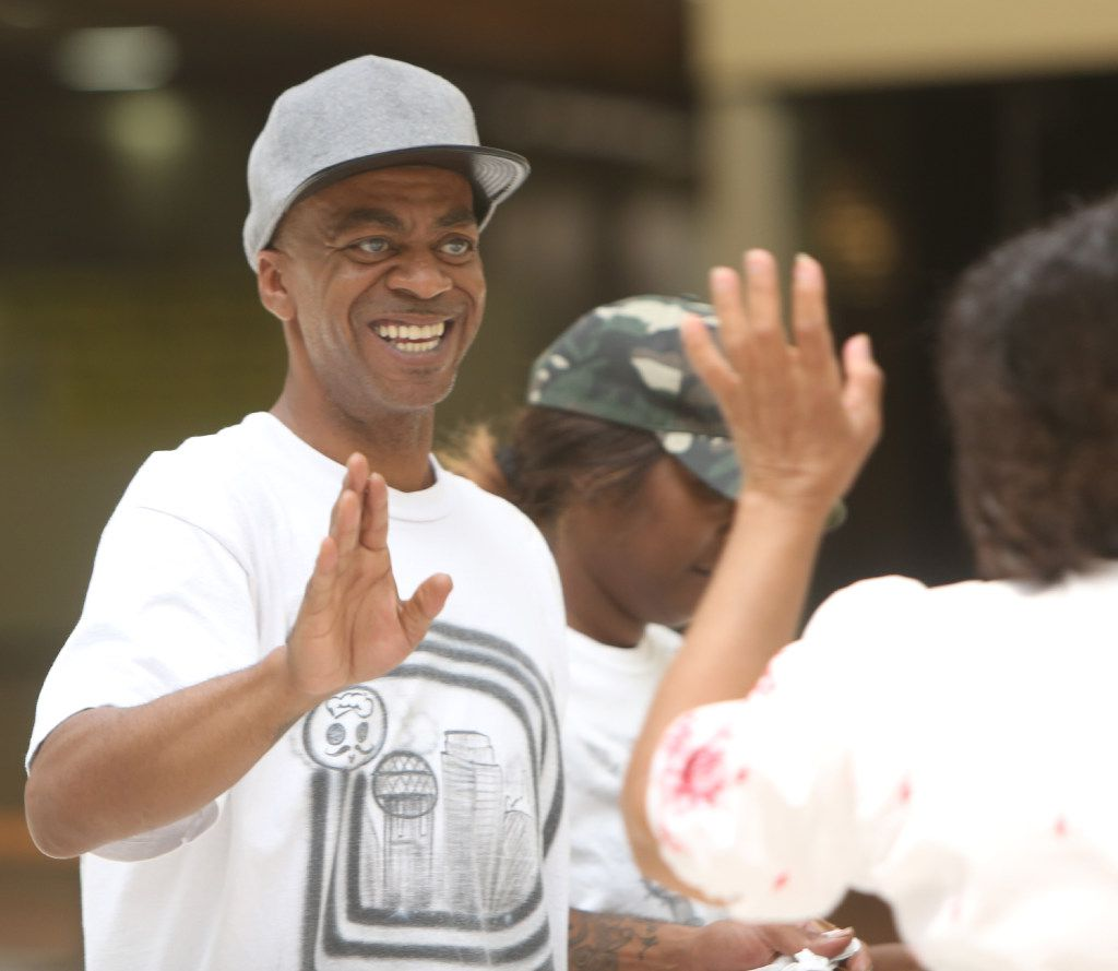 """Demetrious Dee, otherwise known as """"Chef D,"""" shares a smile and a """"high five"""" with a customer delighted with a sample of his food from his booth marketing the wares of his company """"Soul Rolls Catering"""" in Dallas. Dee was one of several small business owners that set up booths to attract the attention of mall guests. The North Texas Black Restaurant Week held its kickoff event at Southwest center Mall in Dallas on May 17, 2017. (Steve Hamm/Special Contributor)"""