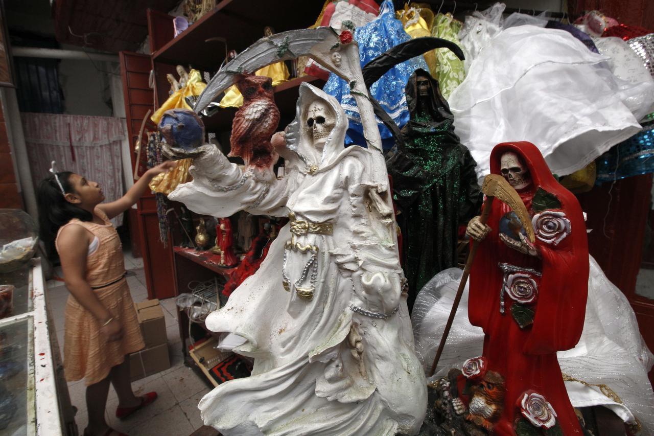 En esta imagen, tomada el 19 de febrero de 2017, una niña coloca imágenes de la Santa Muerte en la iglesia de la Misericordia en el vecindario de Tepito, en la Ciudad de México. (AP/MARCO UGARTE)