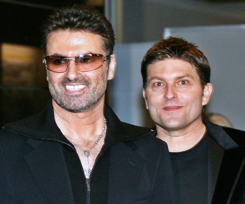"""(FILES) This file photo taken on December 15, 2005 shows British pop star George Michael (L) smiles with his partner Kenny Goss at a reception after the Japan premiere of his autobiographical movie """"George Michael, A Different Story"""" at a restaurant in Tokyo. British pop singer George Michael, who rose to fame with the band Wham! and sold more than 100 million albums in his career, has died aged 53, his publicist said on December 25, 2016. / AFP PHOTO / --/AFP/Getty Images"""