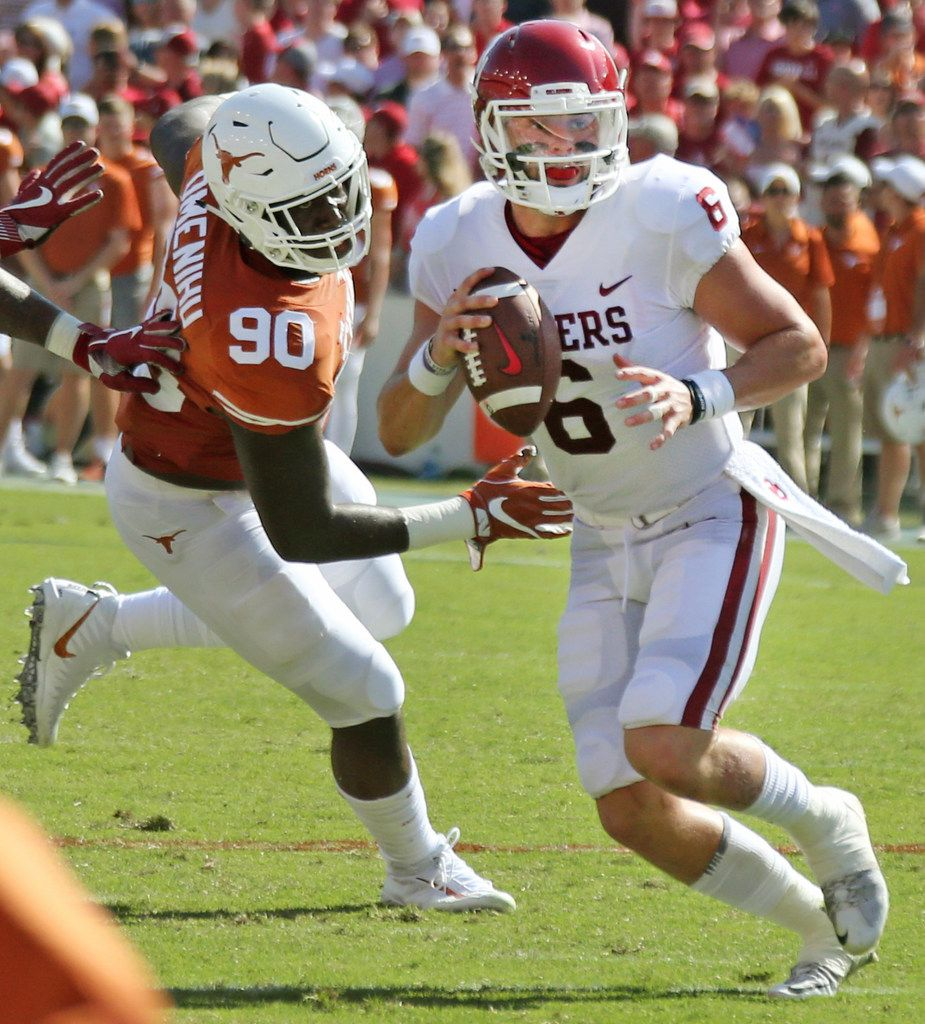 Oklahoma Sooners quarterback Baker Mayfield (6) looks for a receiver as he avoids Texas Longhorns defensive lineman Charles Omenihu (90) during the Oklahoma University Sooners vs. the University of Texas Longhorns NCAA college football game at the Cotton Bowl in Dallas on Saturday, October 14, 2017. (Louis DeLuca/The Dallas Morning News)