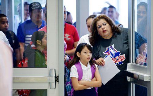 Marta Gómez, maestra bilingüe,  da indicaciones a Merylinn Cabrera, de 7 años en la primaria Joe May.  BRANDON WADE/DMN