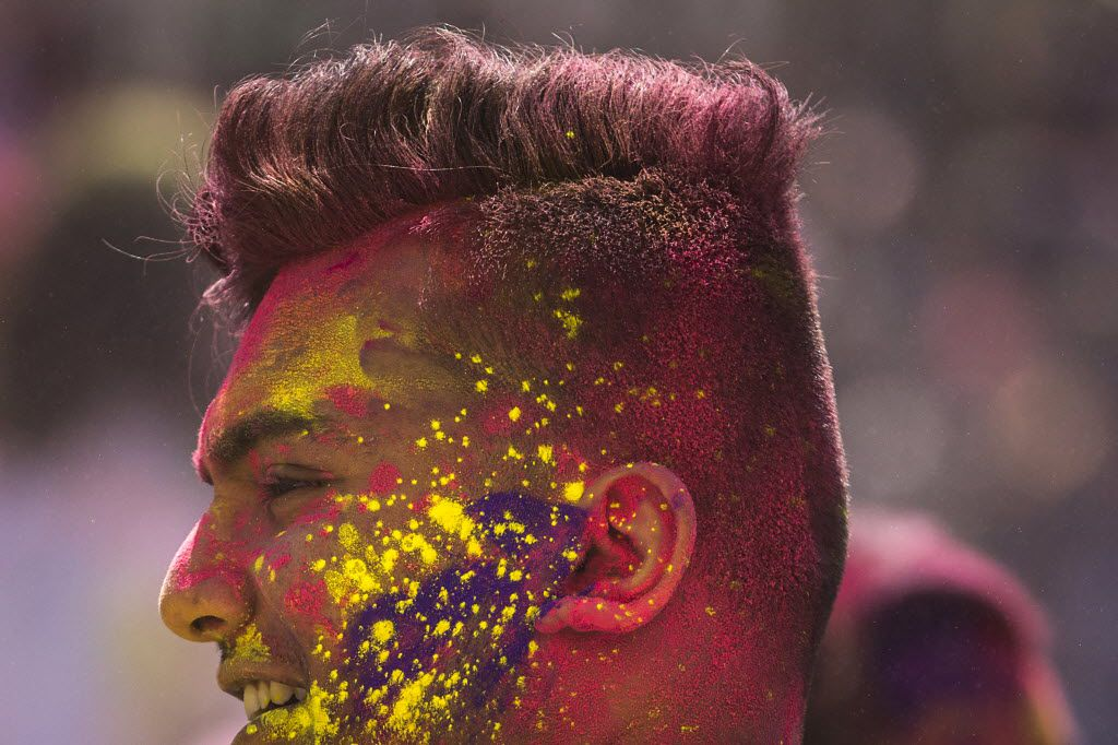 Color covers a man's face during festivities celebrating the Hindu holiday of Holi.