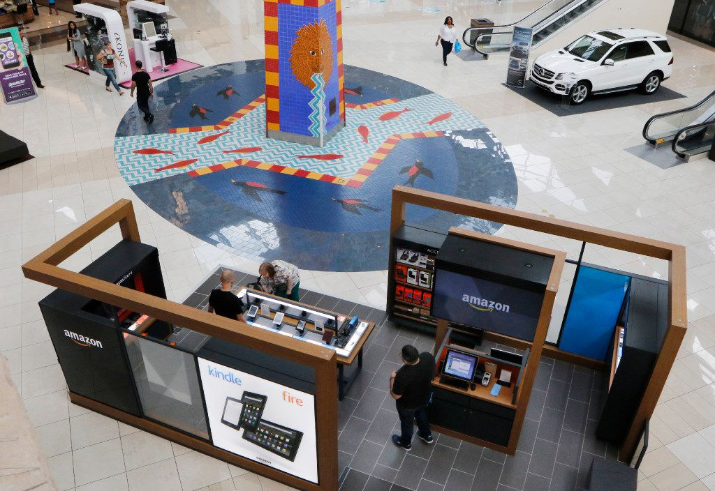 Alec Hall, Retail Experience Manager, left, and Justin Maldonado, Retail Experience Associate, right, help customers shop at Amazon.com Pop-up store located on the first level at the Parks Mall at Arlington, Texas. The store opened August 21, 2016. Photo taken on Wednesday, September 14, 2016. (David Woo/The Dallas Morning News)