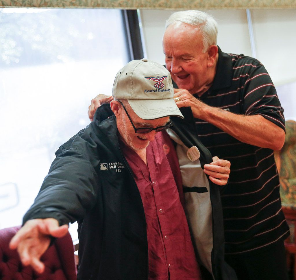 Retired major league umpire Larry Barnett, who has visited hospitalized veterans since 1977, presents a jacket to Russell Moore, a Navy veteran, during a visit to the VA North Texas Health Care System on Thursday, Aug. 8, in Dallas.