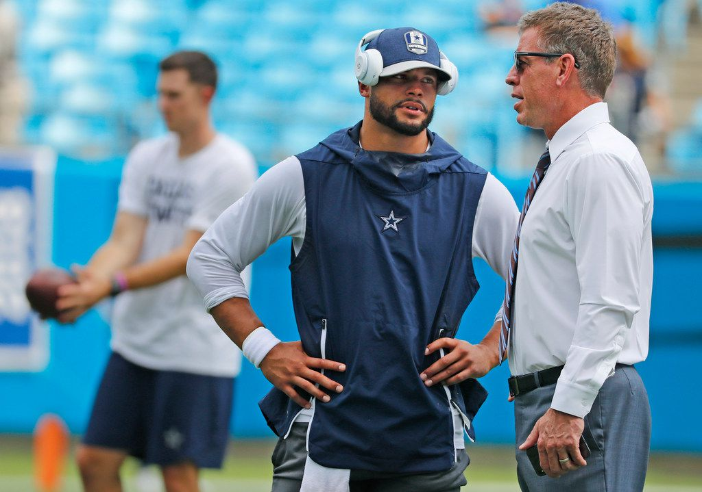 Dallas Cowboys quarterback Dak Prescott (4) talks with TV analyst troy Aikman before the Dallas Cowboys vs. the Carolina Panthers NFL football game at Bank of America Stadium in Charlotte, North Carolina on Sunday, September 9, 2018. (Louis DeLuca/The Dallas Morning News)