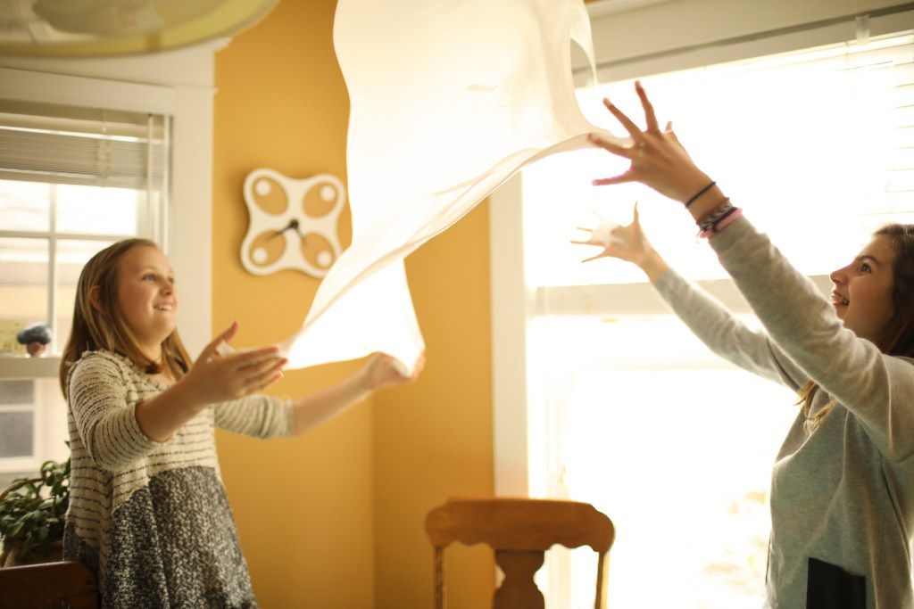 Annabell Sorensen (left) and Petra Lyon, both 12, test the limits of a batch of slime's elasticity by waving it up and down to form a balloon of sorts on April 13, 2017 in Edina, Minn. (Jeff Wheeler/Minneapolis Star Tribune)