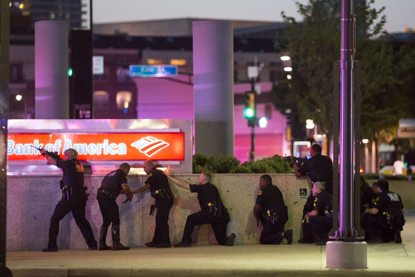 Dallas Police take up a position along a wall at the corner of Lamar at Main streets as they train their weapons toward the El Centro campus after shots were fired following a Black Lives Matter rally in downtown Dallas on July 7, 2016. (Smiley N. Pool/Staff Photographer)