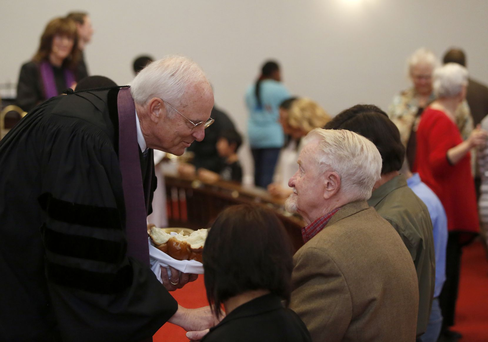 Bill Bryan serves communion at Dallas' Grace United Methodist Church, where he was pastor for more than 12 years. (Guy Reynolds/Staff Photographer)