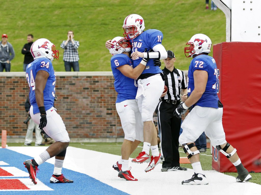 SMU quarterback Garrett Gilbert (11) celebrates his touchdown run with running back Traylon Shead (34), wide receiver Stephen Nelson (6) and offensive lineman Ben Gottschalk (72) in the first overtime period of their American Athletic Conference NCAA foo